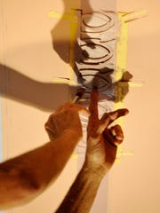 Artist Phil Carroll adds paint to a stencil on the