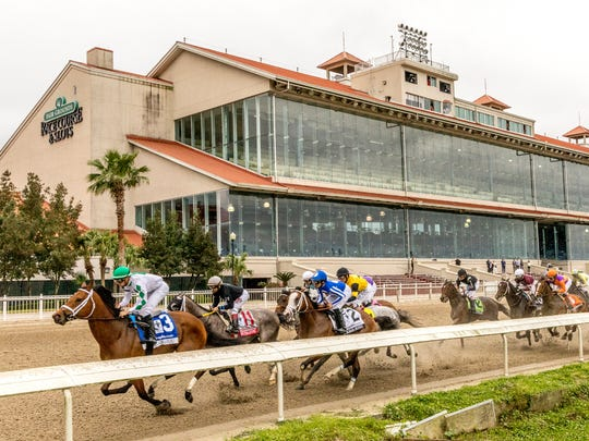 Wells Bayou, left, ridden by jockey Florent Geroux, took an early lead and held off NY Traffic to win he 107th running of the $1,000,000 Grade II Louisiana Derby horse race, Saturday, March 21, 2020, at a fanless Fair Grounds race course in New Orleans. (Amanda Hodges Weir/Hodges Photography, Fair Grounds Race Course via AP)