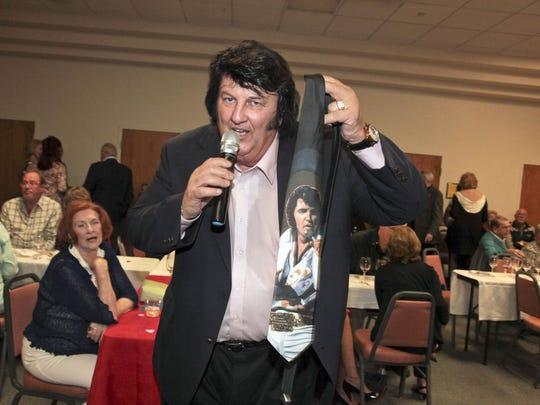 Jack Smink auctions off an Elvis tie — bearing a striking resemblance — during a library benefit in Cocoa Beach.