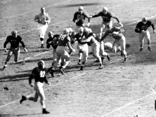 """FILE - In this Nov. 9, 1946, file photo, Army fullback Felix """"Doc"""" Blanchard (35), center left in front of the official, fumbles the ball, in air at center, during the first half against Notre Dame, at Yankee Stadium in New York. Teammate Glen Davis (41), left foreground, recovered the ball. Identifiable Notre Dame players are Bill Fischer (72) and Jim Martin (38)."""