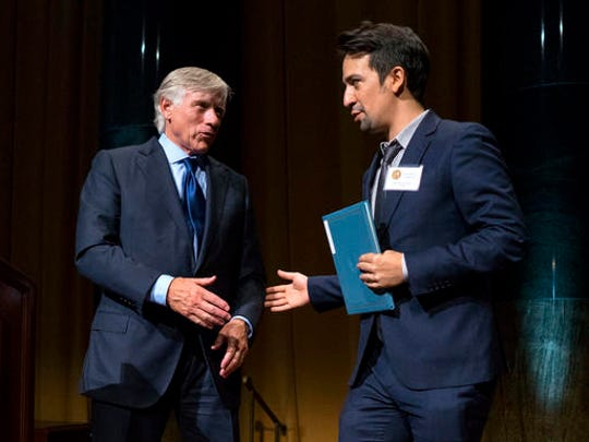 """FILE - In this Oct. 13, 2016 file photo Columbia University President Lee Bollinger, left, reaches out to Lin-Manuel Miranda, who was recognized for the Pulitzer Prize in Drama for """"Hamilton,"""" during the Pulitzer Prize awards at Columbia University in New York.  Miranda, who was everywhere in popular culture this year, was named The Associated Press Entertainer of the Year, voted by members of the news cooperative."""
