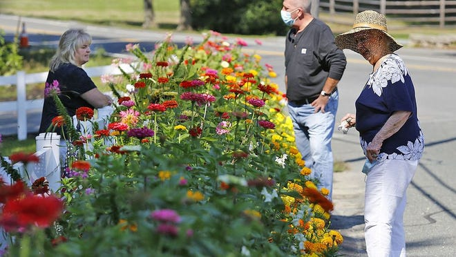 Kelley Brulport, left, and Scott and Dorothy Underdown look over the colorful garden in front of the State Police barracks in Norwell.