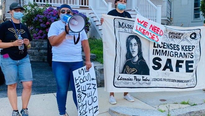 Activists with the Movimiento Cosecha group protest near the home of House Speaker Robert DeLeo on Tuesday morning in support of legislation making driver's licenses available to undocumented immigrants.