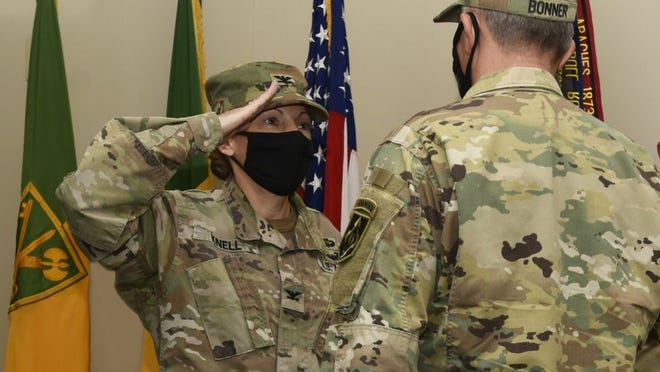 Col. Niave Knell salutes Brig. Gen. James Bonner, Maneuver Support Center of Excellence and Fort Leonard Wood commanding general, as she takes on the roles of commandant of the U.S. Army Military Police School and chief of the MP Regiment today at the John B. Mahaffey Museum Complex's MP Regimental Room.