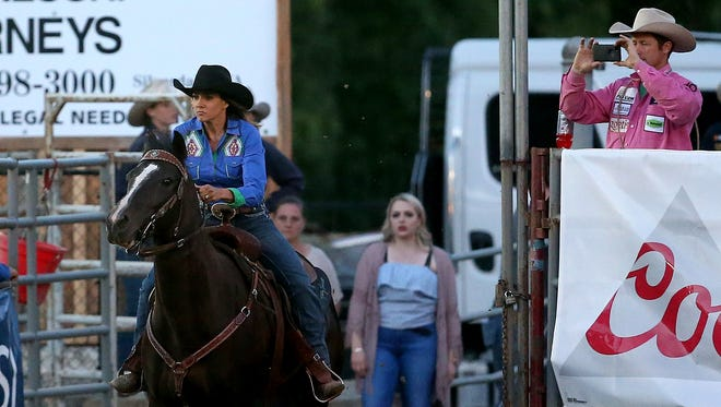 Shea Durfey enters Thunderbird Arena as her husband, Tyson, films her barrel race Thursday at the Kitsap County Fair & Stampede. Tyson, a tie-down roper, and Shea are competing while raising a 1-year-old daughter, Praise Royal.