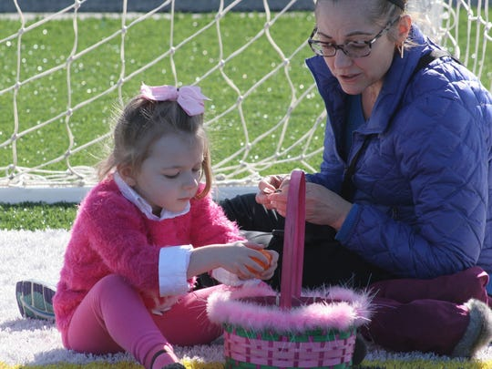 Melissa Jolly and daughter Emersen Jolly-Grigoriou, 3, examine their hoard. Everyone was limited to six eggs each but some left with fewer.