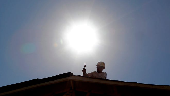 FILE - In this July 25, 2014 file photo, a roofer works under the mid-day sun in Gilbert, Ariz. Federal science officials announced Friday that for the third time in a decade, the globe sizzled to the hottest year on record. Both the National Oceanic and Atmospheric Administration and NASA calculated that in 2014 the world had its hottest year in 135 years of record-keeping. Earlier, the Japanese weather agency and an independent group out of University of California Berkeley also measured 2014 as the hottest on record. (AP Photo, File)