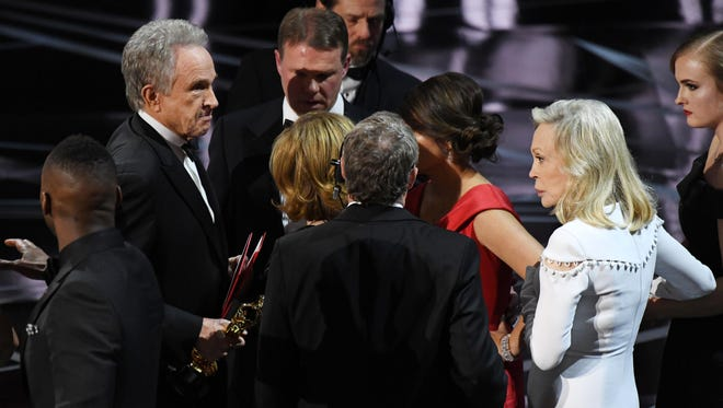 Warren Beatty, Faye Dunaway and a clutch of confused academy officials mill around on stage after the great Oscars flub of the 2017 Academy Awards, Feb. 26, 2017.