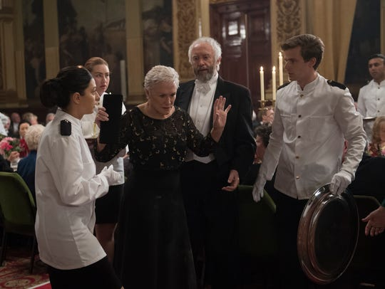 "After Joe (Jonathan Pryce, center) receives his Nobel Prize, Joan (Glenn Close) leaves the celebratory dinner in frustration in ""The Wife."""