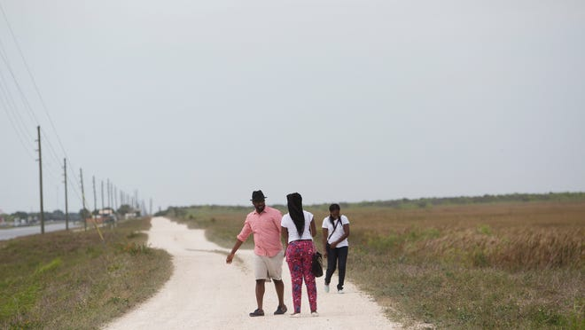 Marc Dely, left, Fabiola Joseph and Zaelle Formue walk along a berm that parallels Tamiami Trail that may be part of a proposed bicycle trail that will connect Naples to Miami.