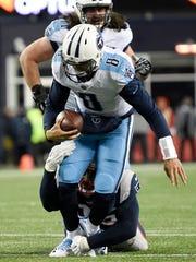 Titans quarterback Marcus Mariota (8) is pulled down