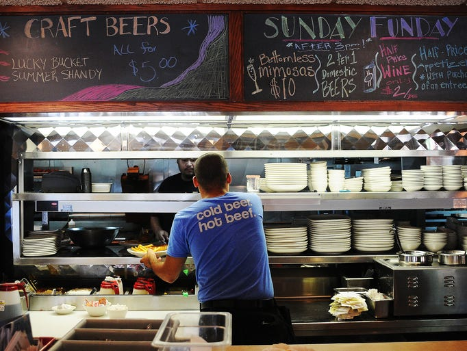 Josh Davis, who has worked at the Phillips Avenue Diner less than a month, grabs an order for a customer on Monday, July 7, 2014, at the Diner in downtown Sioux Falls, S.D. The Phillips Avenue Diner has hired more employees after seeing business increase with the number of new companies moving in downtown.Ê