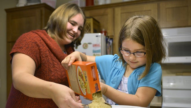 Kaitlyn Reichel, 6, works with her mom, Cindy,  to make a Mexican rice recipe together in their Sartell apartment. They have entered a stuffed poblano pepper in Uncle Ben's Rice Beginners Contest. If they are one of the five winners, Kaitlyn's elementary school would receive a cafeteria makeover and her family would get $15,000.