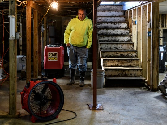David Melton takes a moment to rest after a long day of drying out and disinfecting the basement at his home in Reed, Ky., Friday, March 16, 2018. Repairing the basement was the first major project in the Meltons' flood recovery process because their electric panel and hot water heater are located there. Their 11-year-old daughter Jessie's bedroom was also located in the basement (room on right), but she has now converted the upstairs home office into a bedroom.