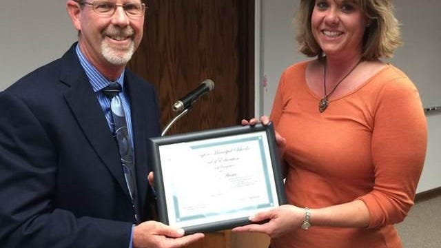 Kyle Rhodes, president of the Farmington Municipal School District Board of Education, presented Brandy Acosta with the school district's 'Teacher of the Year' award on Oct. 8. Acosta teaches fifth grade at Apache Elementary School.