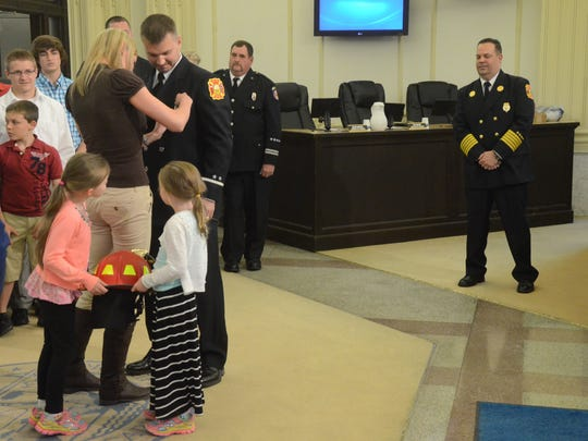 While his wife, Leah, pins his badge, daughters Zurie,
