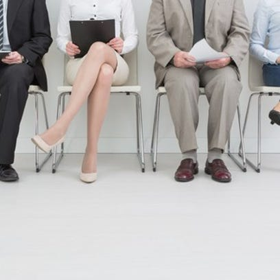 Two women and two men sitting in chairs in a line