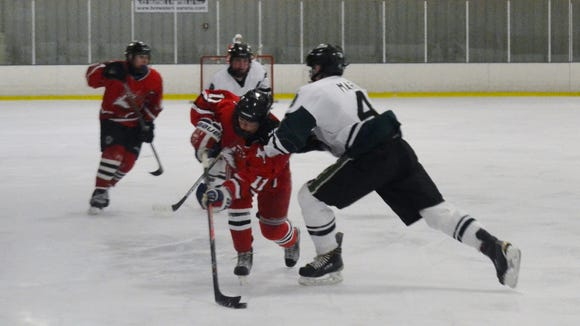 Fox Lane freshmen Trevor Zegras takes a hit from Thomas Mark (4) and continues up the ice during a 4-2 playoff loss to Brewster on Feb. 11, 2016 at Brewster Ice Arena.