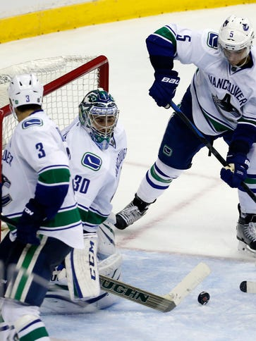 The puck bounces in the crease in front of Vancouver