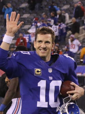 Eli Manning celebrates his team's win as he runs off the field at the end of the game.