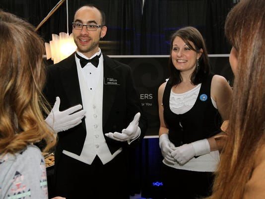 Jason and Sandy Holland, from Fairview Township take the idea of travel butlers so seriously that they even dress the part. Here, they speak with soon-to-be brides during the AACA Museum Wedding Show in Hershey in February.