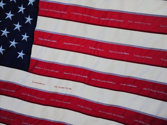 Names of all 49 victims are embroidered to a U.S. flag at a memorial at the Dr. Phillips Center for the Performing Arts Thursday, June 16, 2016 in Orlando, Fla.