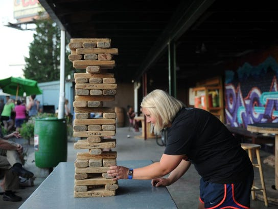 Allison Miller plays a game of Jenga at Bearden Beer Market off of Kingston Pike on June 7.