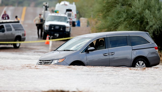 A vehicle sits in the middle of Skunk Creek  near 19th Avenue and Desert Hills Drive Tuesday, Oct. 20, 2015, after getting stuck.  The driver was safely rescued.
