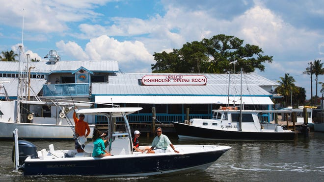 A boat rides past Kelly's Fish House last week. Naples' longest-running restaurant will close this summer. A new waterfront promenade will go on the property, with outdoor dining, boat rentals and underground parking.