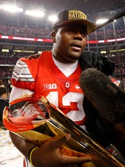 Ohio State quarterback Cardale Jones holds the national championship trophy after the Buckeyes beat Oregon 42-20 in the College Football Playoff title game.