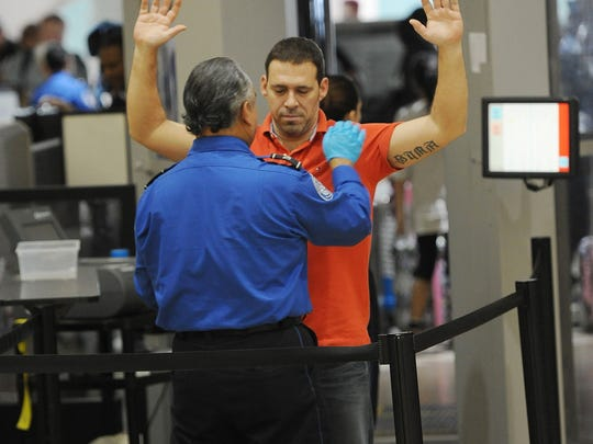 An air traveler is patted down after passing through a full-body scanner at the TSA  security checkpoint at  Los Angeles International Airport on Feb. 20, 2014.