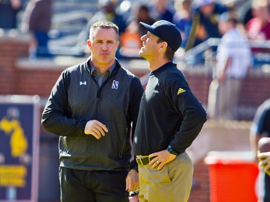Northwestern head coach Pat Fitzgerald, left, talks with Michigan head coach Jim Harbaugh, right, before their NCAA college football game in Ann Arbor, Mich., Saturday, Oct. 10, 2015. (AP Photo/Tony Ding)