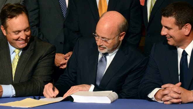 Democratic Gov. Tom Wolf signs legislation designed to reduce long-term public pension costs during a signing ceremony in the Pennsylvania Capitol on Monday, June 12, 2017 in Harrisburg, Pa. Looking on are Senate Majority Leader Jake Corman, R-Centre, left, and House Majority Leader Dave Reed, R-Indiana.