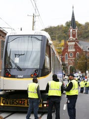 The first streetcar is delivered by a tractor trailer