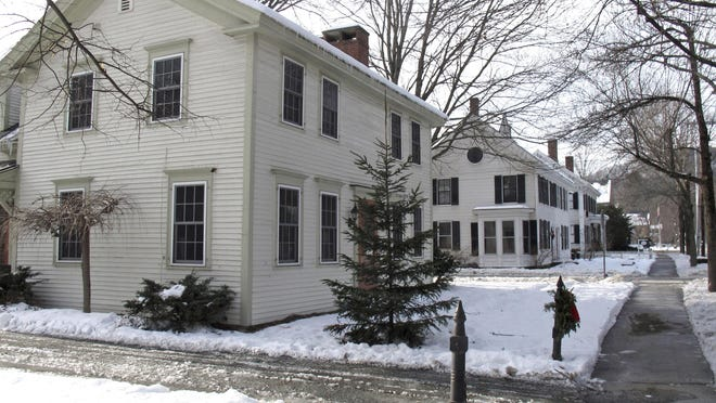 In this photo taken Dec. 20, 2016, a home with shutters, at right, is next to a home without shutters, at left, in Woodstock, Vt. The village of Woodstock is cracking down on homeowners who are refusing to keep shutters on their homes. Officials say the loss of shutters would hurt the village's historic character.