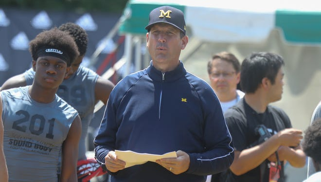 Michigan coach Jim Harbaugh watches students compete during the Sound Mind Sound Body football camp held at Wayne State on Friday, June 10, 2016