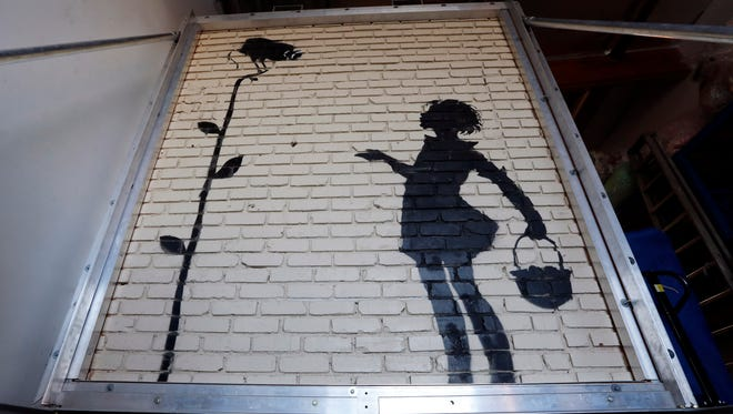 """""""Flower Girl,"""" a stencil on a massive brick wall by popular street artist Banksy, is displayed in a warehouse in Los Angeles."""