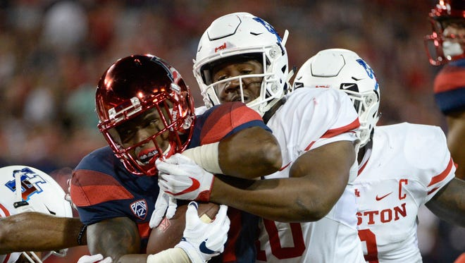 Arizona Wildcats running back Zach Green (34) is tackled by Houston Cougars defensive tackle Ed Oliver (10) during the first half at Arizona Stadium.