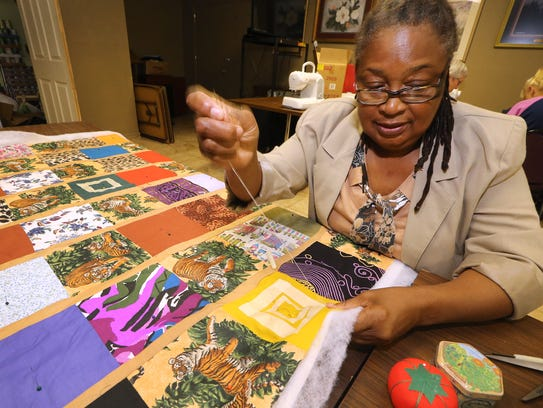 Jacquelyn Latimore hand quilts her project during a