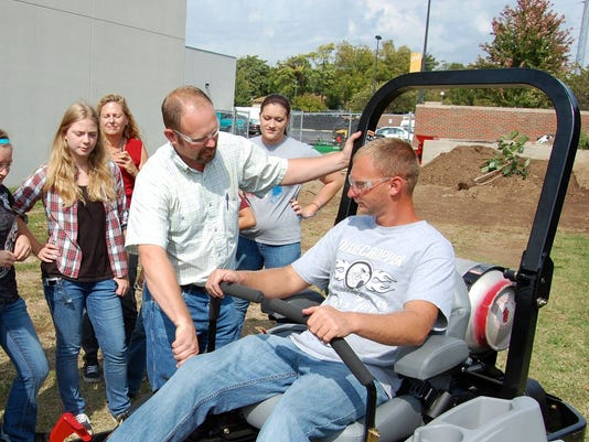 Rob Flatness (standing next to mower) talks to students about the new device.jpg