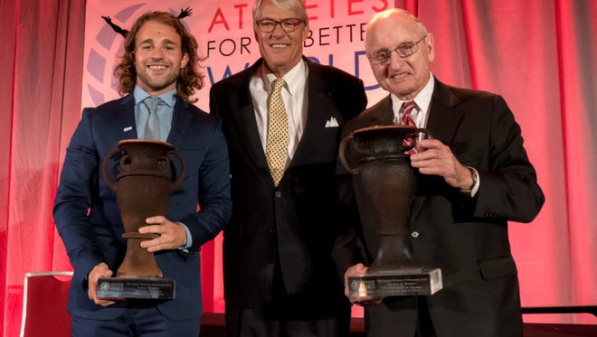 Denison football and track athlete Luke Romick (left) receives the prestigious Coach Wooden Citizenship Cup in Atlanta from founder and Athletes for a Better World President Fred Northrup (center). Former Georgia football coach Vince Dooley (right) was professional athlete winner.