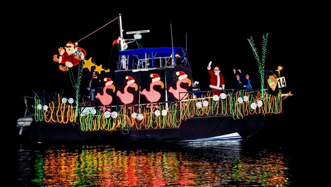 A boat decorated in a pink flamingo theme makes its way through Ventura Harbor during the 2016 Parade of Lights.