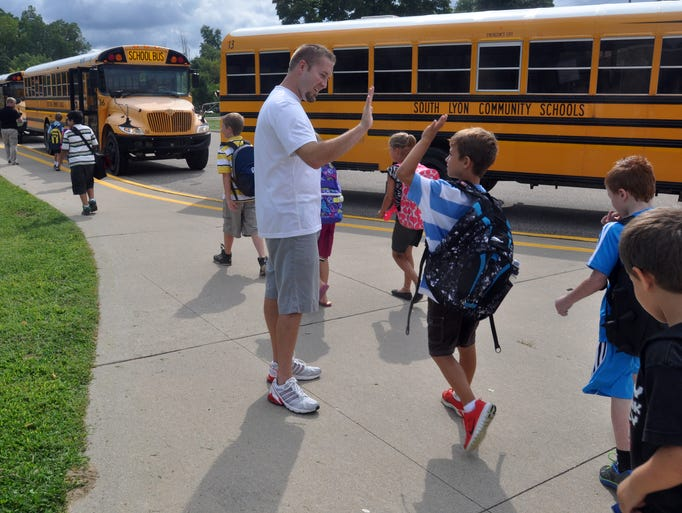 Kids head out to their buses and give Matt Naudi the phys. ed. teacher a high five  at Bartlett Elementary on the first day of school.