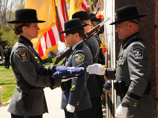Manchester police prepare to present the American flag to the family of Officer Scott R. Thompson, who was posthumously promoted to corporal.