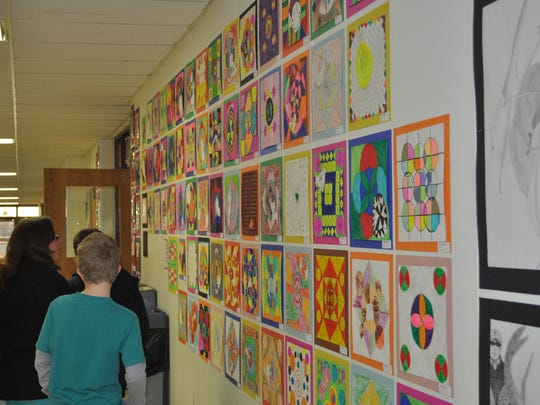 Visitors look over student-created art on exhibit in a Southern Door Schools hallway at a past Southern Door Fine Arts Festival. The 15th annual festival takes place April 9 at the school.