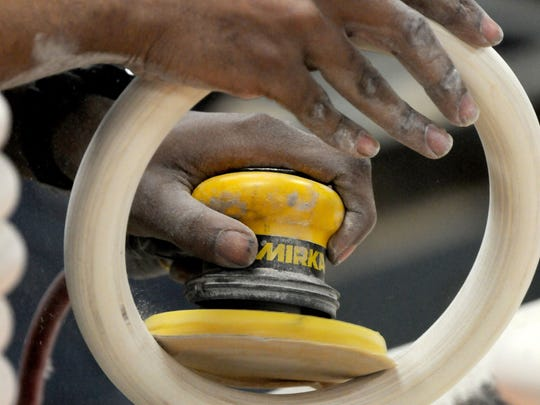 A worker at Cooper Enterprises sands a ring used for athletic equipment.