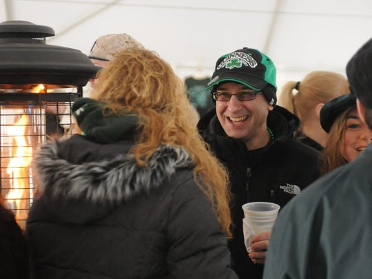 Greg DiMiceli, center, of Highland Mills, hangs out near the fire with friends at the Paddy on the River event in Beacon.