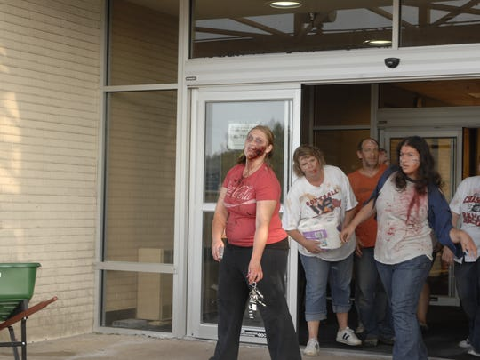 Members of the Superational Loves the Lone Enchiladas team, dressed and in character as zombies, leave Shopko after purchasing toilet paper, one of the items on their scavenger hunt list.
