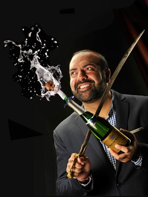"""PHOTO ILLUSTRATION Vivek Surti uses a saber to perform the art of """"sabrage"""" to open bottles of champagne with a flourish.   Wednesday Jan. 27, 2016, in Nashville, Tenn. PHOTO ILLUSTRATION by Larry McCormack"""