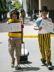 Fez Zafar, left, 12, and Ryan Larson, 12, both of Clive, wear costumes to help create a buzz as they sell water and other cold beverages in a entrepreneurship competition.